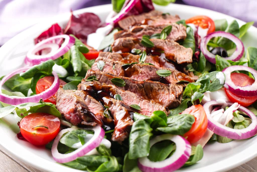 closeup of steak salad with red onions and tomatoes