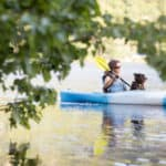 A woman in a blue and white kayak with her dog