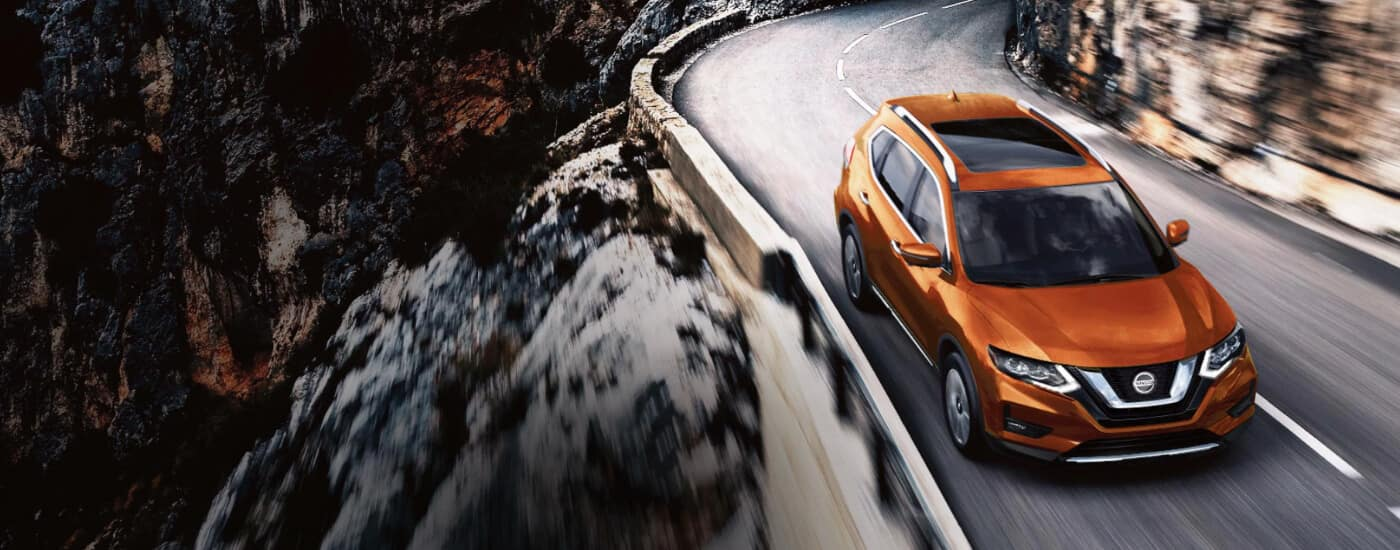orange 2020 Nissan Rogue driving on windy cliff road