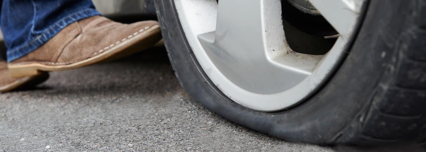 motorist-kicking-deflated-tire