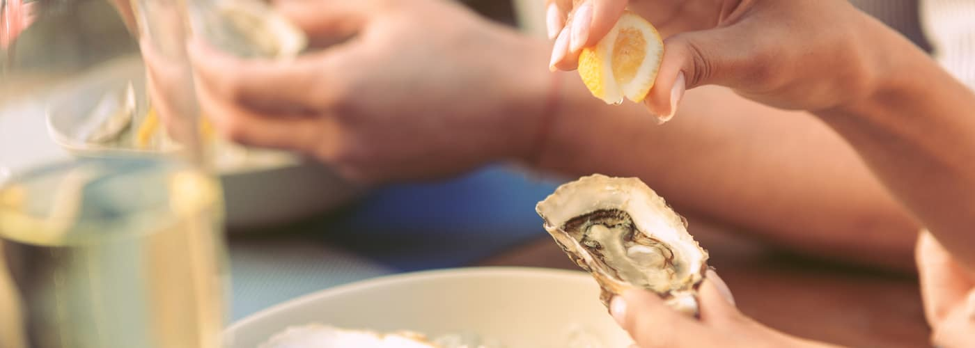 woman squeezing lemon over oyster