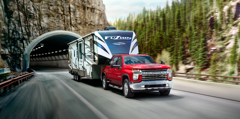 2020 chevy silverado 2500hd red exterior driving down road pulling trailer