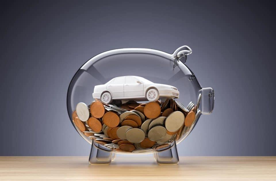 Model Car on money inside transparent piggy bank