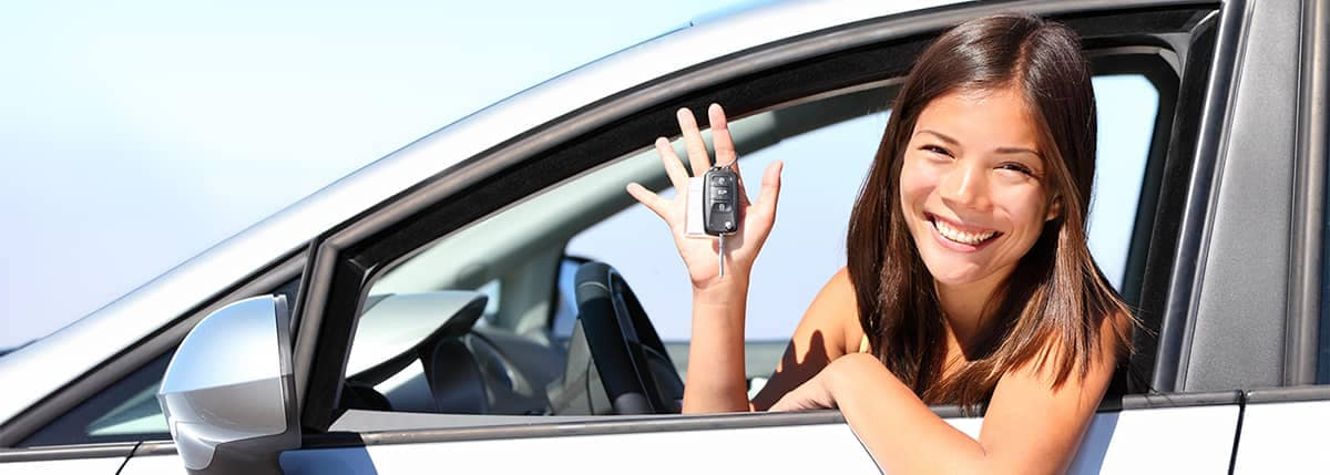 Excited young female holding keys in drivers seat
