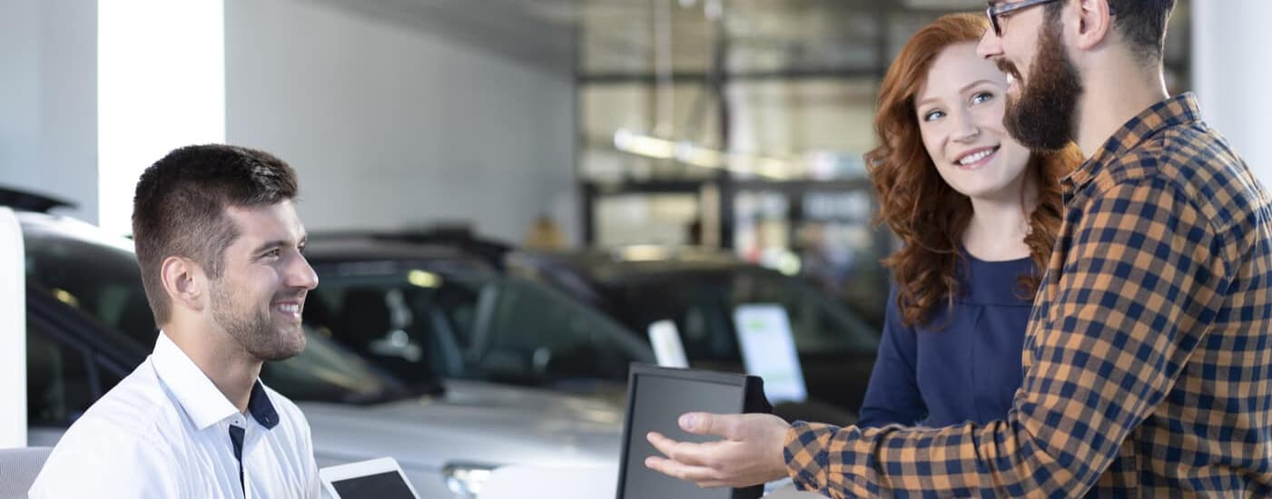 Excited Couple Reviewing Trade in Offer with Salesman