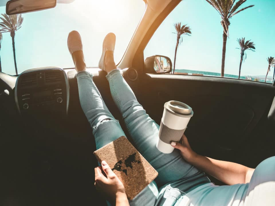 Woman holding coffee and a map, feet propped on dashboard on a summer road trip