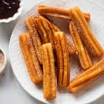 A plate of churros next to dishes of cinnamon sugar and chocolate sauce
