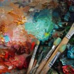 paint brushes over a palette of various colors