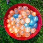 Full water balloons in a red bucket on green grass