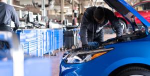Mechanic working under hood of blue car